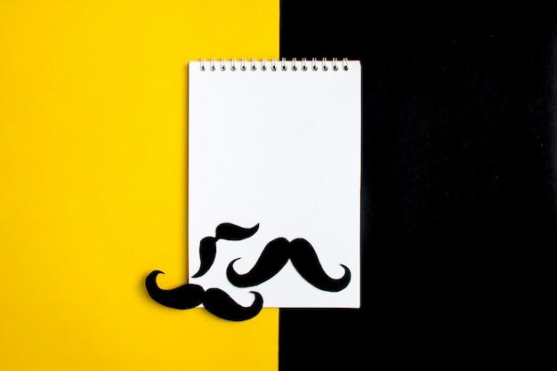 Bigode de papel preto, bloco de notas, lápis, fundo amarelo mês doações controle de prosta Foto Premium