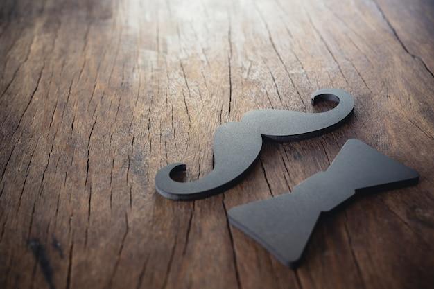 Bigode masculino e laço preto colocados no chão de madeira velho Foto gratuita