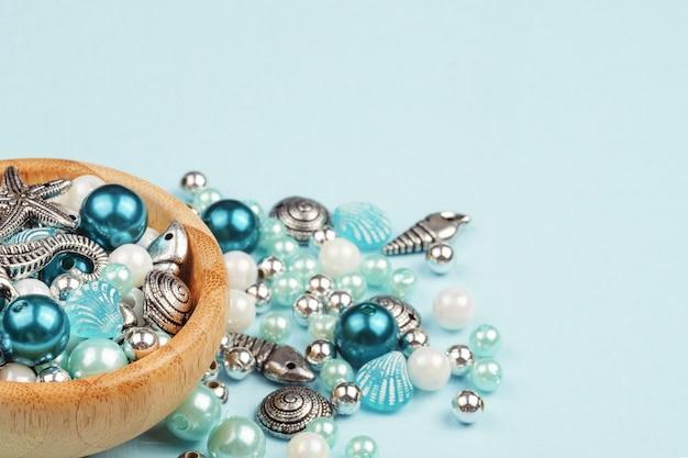 Bijuteria. fazendo colares de contas. fundo azul Foto Premium