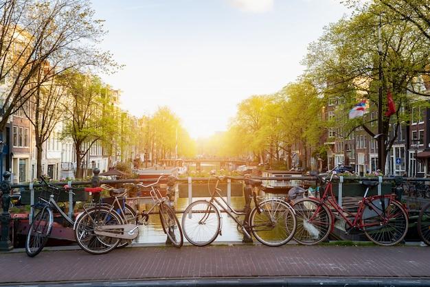 Bike sobre a cidade de amsterdão do canal em países baixos com vista no rio amstel durante o por do sol. Foto Premium