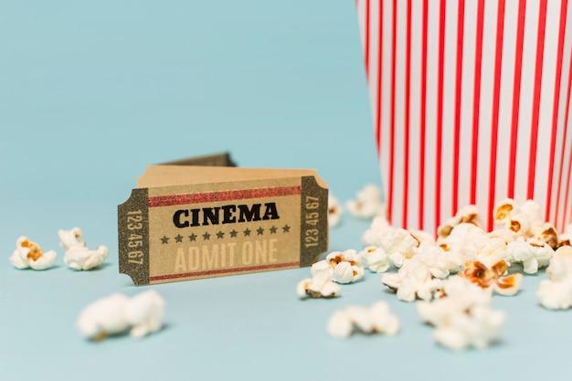 Bilhete de cinema perto das pipocas contra o fundo azul Foto gratuita