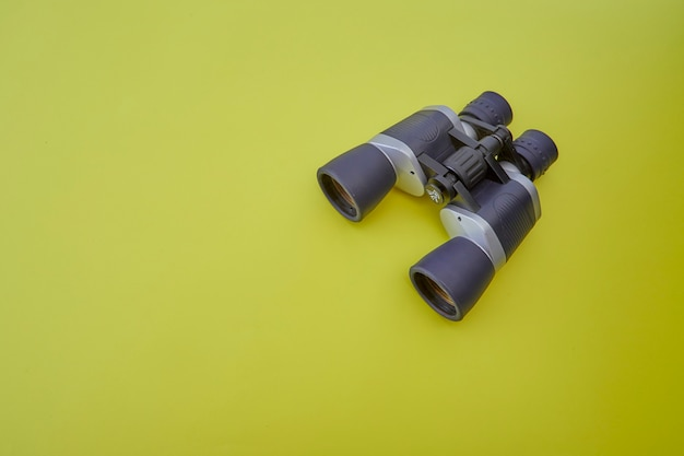 Binóculos prata e cinza em fundo amarelo Foto Premium