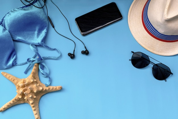 Biquíni de maiô, chapéu, telefone, óculos de sol e estrela do mar azul Foto Premium
