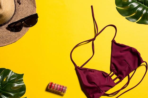 Biquíni, folhas e chapéu amarelo Foto gratuita
