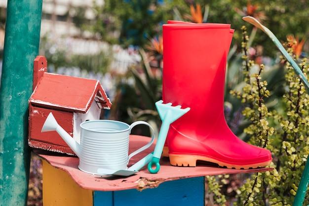 Birdhouse com botas vermelhas wellington; regador; ferramentas de jardinagem no jardim Foto gratuita