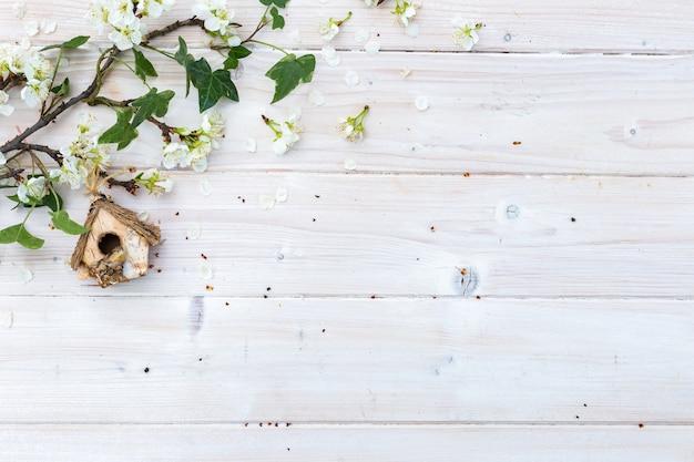 Birdhouse e galhos com flores em uma mesa de madeira com copyspace Foto gratuita