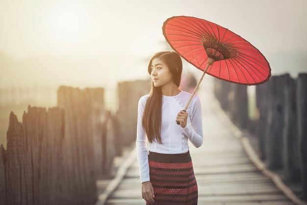 Birmanês, mulheres, em, birmanês tradicional, vestido, com, guarda-chuva vermelho Foto Premium