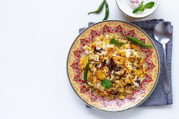 Biryani de frango indiano halal servido com iogurte de tomate raita Foto Premium