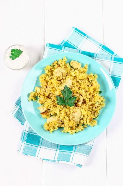 Biryani indiano com frango, iogurte e especiarias em um prato na mesa de madeira. ano novo, prato de natal Foto Premium