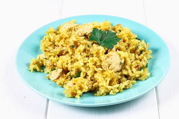 Biryani indiano com frango, iogurte e especiarias no prato na mesa de madeira. ano novo, prato de natal Foto Premium