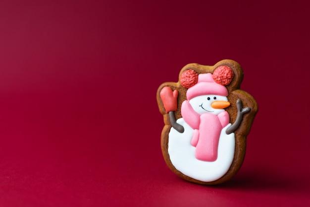 Biscoito de gengibre de boneco de neve bonito no vermelho Foto Premium