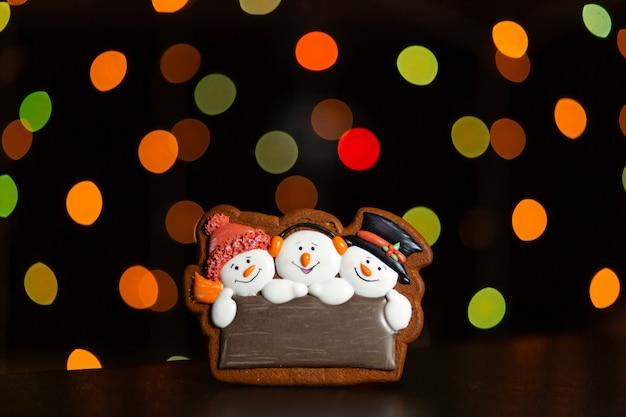 Biscoito de gengibre do retrato de três boneco de neve sobre luzes coloridas borradas de guirlanda Foto Premium