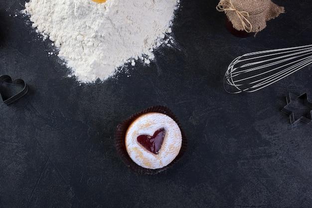 Biscoito de pastelaria com um coração vermelho jam e açúcar em pó de confeiteiro Foto Premium
