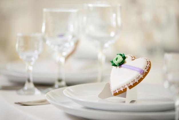 Biscoito em forma de coração coberto com esmalte doce, decorado com flores verdes e minúsculos padrões em pratos brancos como decoração para mesa festiva de casamento perto das taças de vinho Foto gratuita