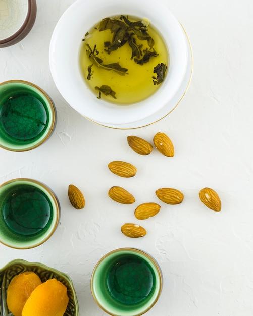 Biscoitos; amêndoas com chá de ervas e xícaras no fundo texturizado branco Foto gratuita