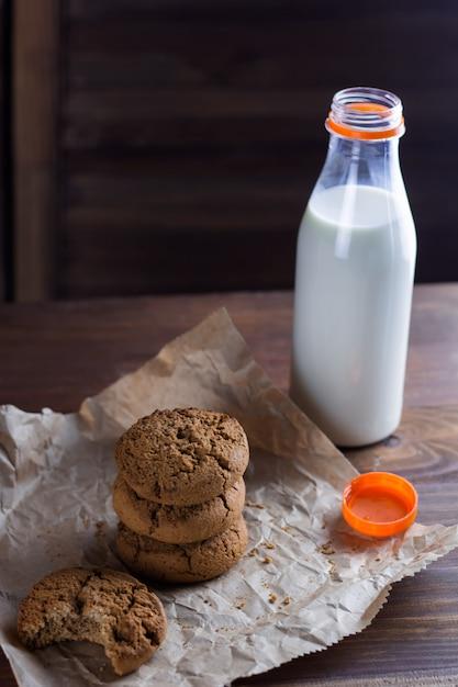 Biscoitos caseiros e fundo de madeira de garrafa de leite Foto Premium
