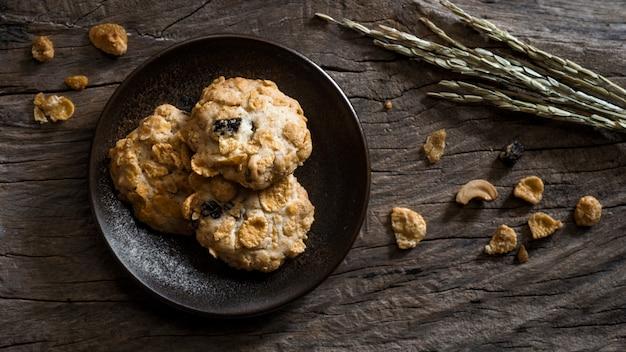 Biscoitos caseiros na placa, cereais e biscoitos de passas padaria na mesa de madeira Foto Premium