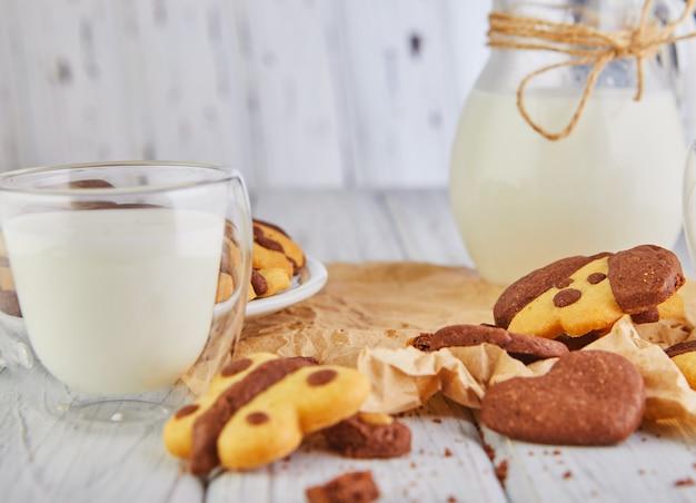 Biscoitos caseiros simples de biscoito amanteigado em forma de cães e borboletas com um copo de leite Foto Premium