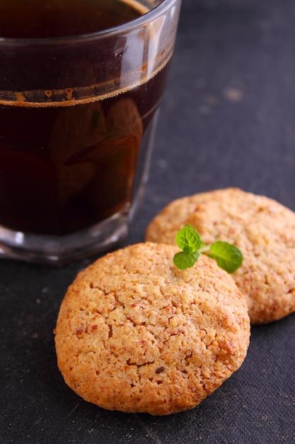 Biscoitos de amêndoa em um fundo preto com uma xícara de café Foto Premium