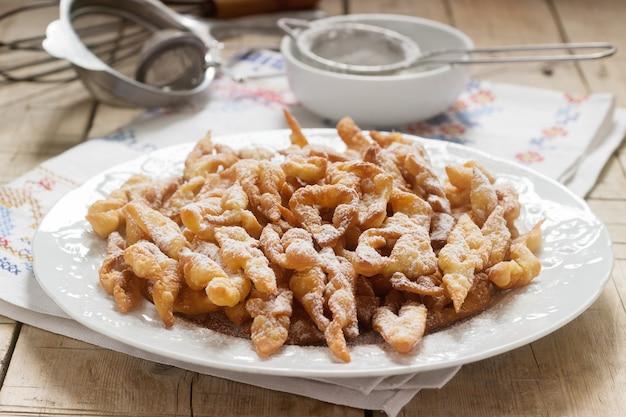 Biscoitos de asas de anjo, um prato doce europeu tradicional para o carnaval. estilo rústico. Foto Premium