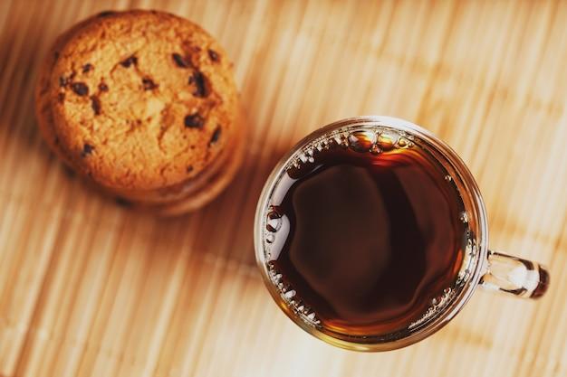 Biscoitos de aveia com pedaços de chocolate e uma caneca de chá preto aromático em um substrato de bambu Foto Premium