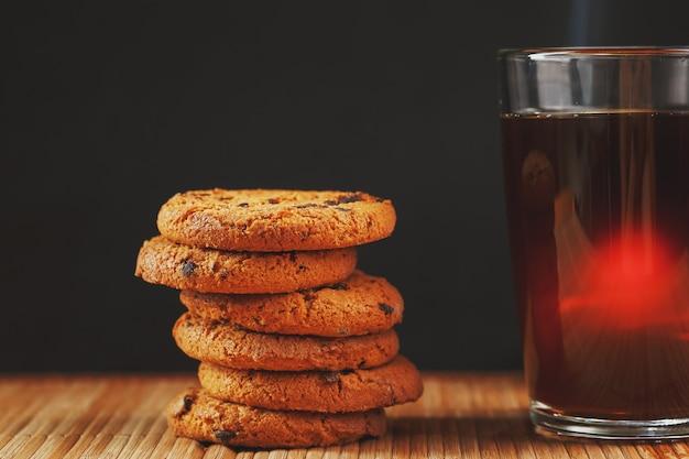 Biscoitos de aveia com pedaços de chocolate e uma caneca de chá preto aromático Foto Premium