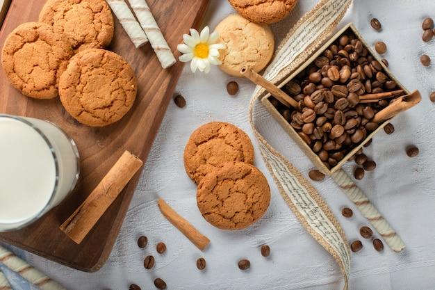 Biscoitos de aveia com um copo de leite e caixa de grãos de café. Foto gratuita
