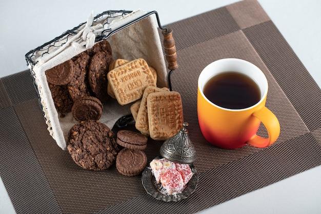 Biscoitos de cacau e manteiga em uma cesta com uma xícara de chá Foto gratuita