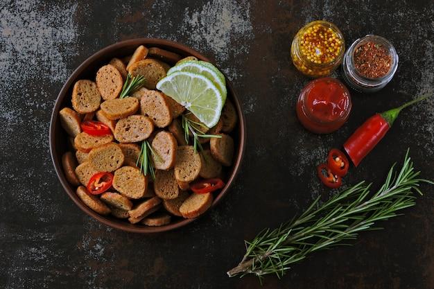 Biscoitos de centeio crocantes em uma tigela com especiarias. configuração plana. Foto Premium