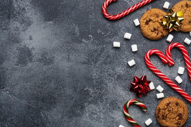 Biscoitos de chocolate bastões de natal caramelo cenário ouro vermelho e marshmallow em cinza escuro. quadro de copyspace. Foto Premium