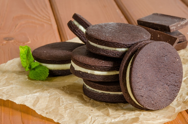 Biscoitos de chocolate com creme de manteiga. biscoitos caseiros de oreo com um copo de leite. Foto Premium