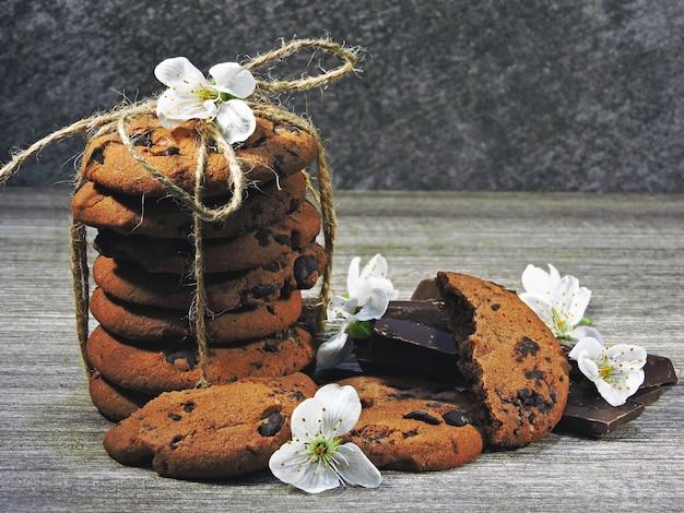 Biscoitos de chocolate e flores brancas. Foto Premium