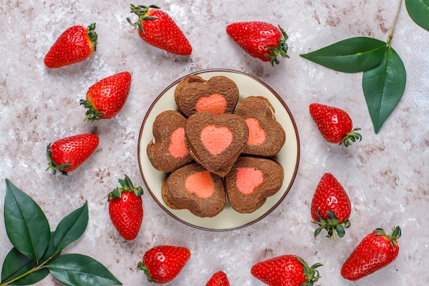 Biscoitos de chocolate e morango em forma de coração com morangos frescos, vista superior Foto gratuita