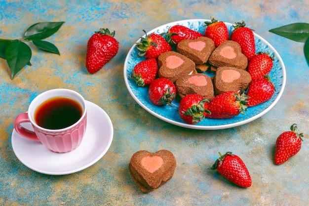 Biscoitos de chocolate e morango em forma de coração com morangos frescos Foto gratuita