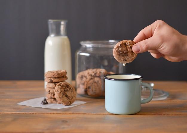 Biscoitos de chocolate em frasco de vidro com garrafa de vidro de leite e caneca de esmalte turquesa na mesa rústica de madeira com a mão de homens segurando um cookie Foto Premium