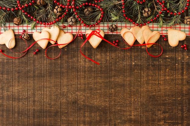 Biscoitos de coração com galhos verdes e cones Foto gratuita