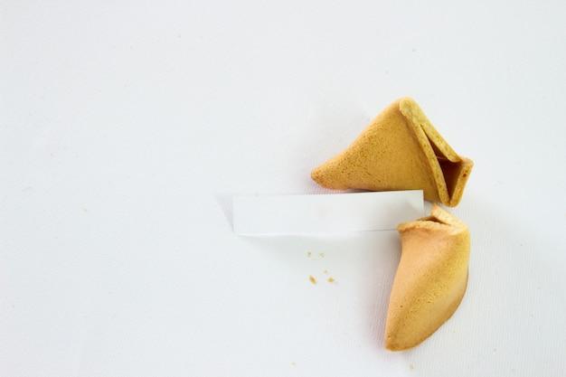 Biscoitos de fortuna quebrada com deslizamento em branco isolado no fundo branco Foto gratuita