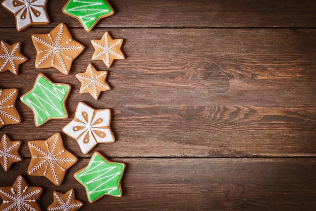 Biscoitos de gengibre de natal em forma de estrelas encontra-se em um fundo de madeira. Foto Premium