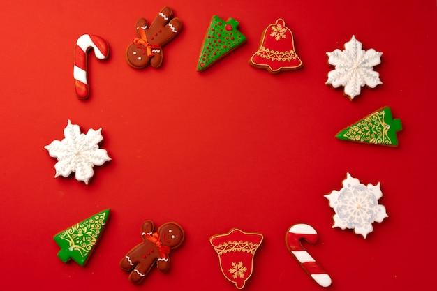 Biscoitos de gengibre de natal na vista superior de fundo vermelho, copie o espaço Foto Premium