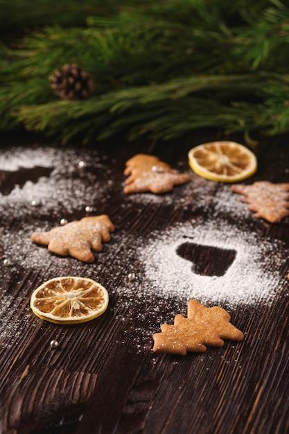 Biscoitos de gengibre em forma de abeto e coração de natal, açúcar em pó na mesa de madeira, frutas cítricas secas, galho de árvore do abeto, vista de ângulo, foco seletivo Foto Premium
