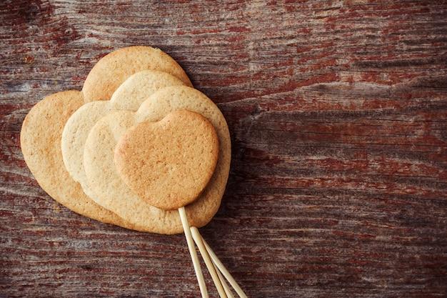 Biscoitos de gengibre em uma vara em forma de corações em um fundo de madeira. vista do topo Foto Premium