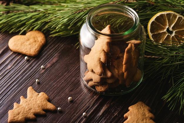 Biscoitos de gengibre forma de abeto e coração de natal em frasco de vidro brilhante na mesa de madeira, limão cítrico seco, galho de árvore do abeto, vista de ângulo, foco seletivo Foto Premium