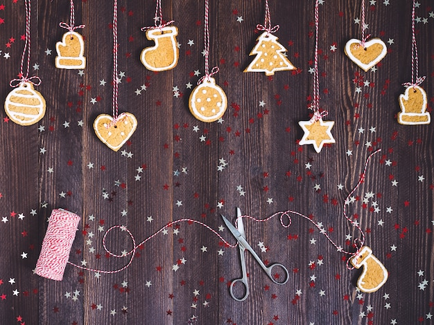 Biscoitos de gengibre na corda para a decoração da árvore de natal com tesoura e fio de ano novo na mesa de madeira Foto gratuita
