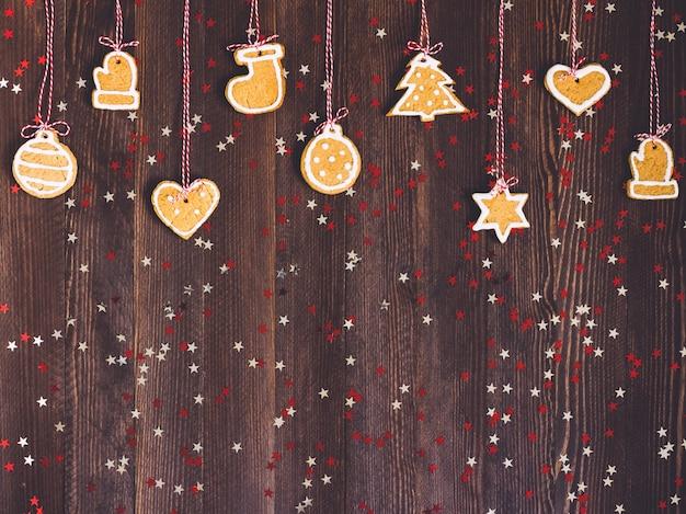 Biscoitos de gengibre na corda para a decoração da árvore de natal reveillon na mesa de madeira Foto gratuita