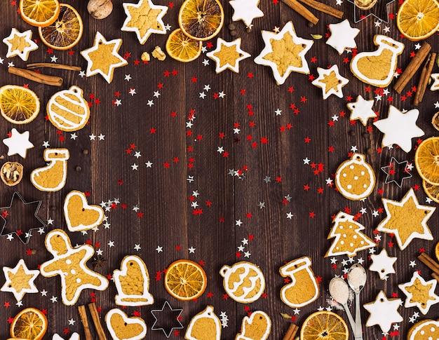 Biscoitos de gengibre natal ano novo laranjas canela na mesa de madeira com copyspace Foto gratuita