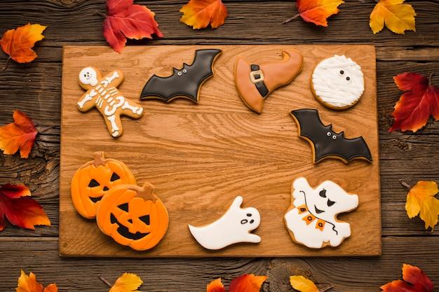 Biscoitos de halloween de vista superior em uma placa de madeira Foto gratuita