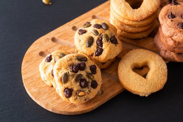 Biscoitos de manteiga de açúcar caseiro de conceito de comida na placa de madeira na placa de pedra ardósia preta com espaço de cópia Foto Premium