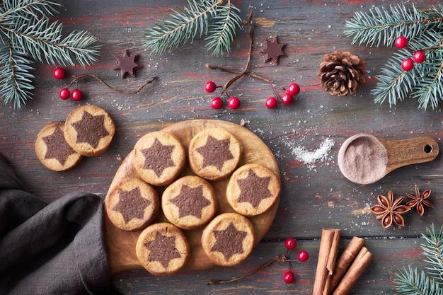 Biscoitos de natal com padrão de estrela de chocolate com estrelas de chocolate, canela e galhos de pinheiro decorado Foto Premium