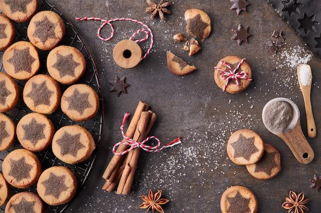 Biscoitos de natal com padrão de estrela de chocolate no rack de refrigeração com especiarias Foto Premium