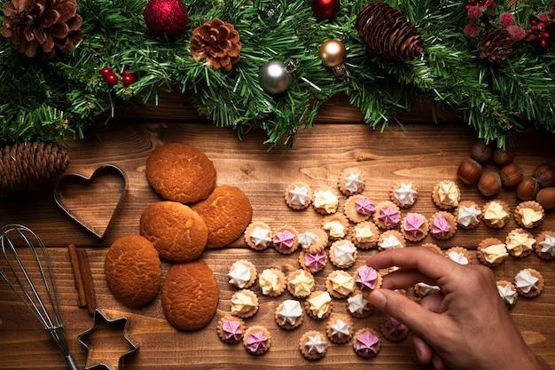 Biscoitos de natal de vista superior com fundo de madeira Foto gratuita